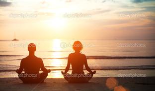 молодая пара в позиция лотос на пляже закат