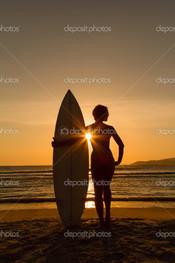 серфингистка на пляже в закат