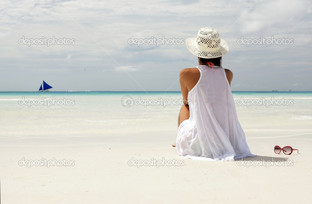 девушка на пляже смотрит на горизонт
